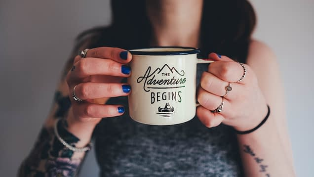 hands holding a mug saying the adventure begins for a post about how to start a sex blog