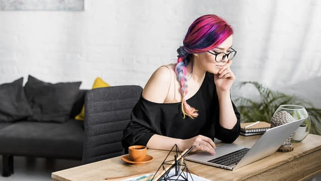 femme person with pink and purple hair sitting at table looking laptop while writing
