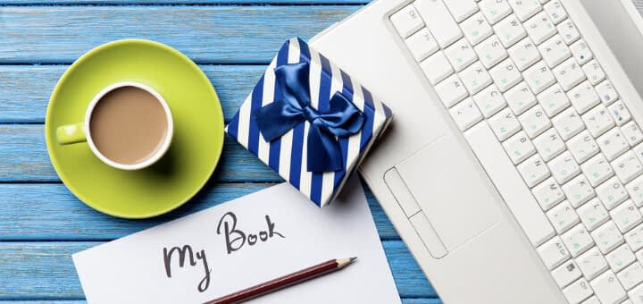 image of laptop, cup of coffee, pen, open journal titled my book, and gift wrapped in white and blue paper with a blue ribbon showing different options for gifts for writers