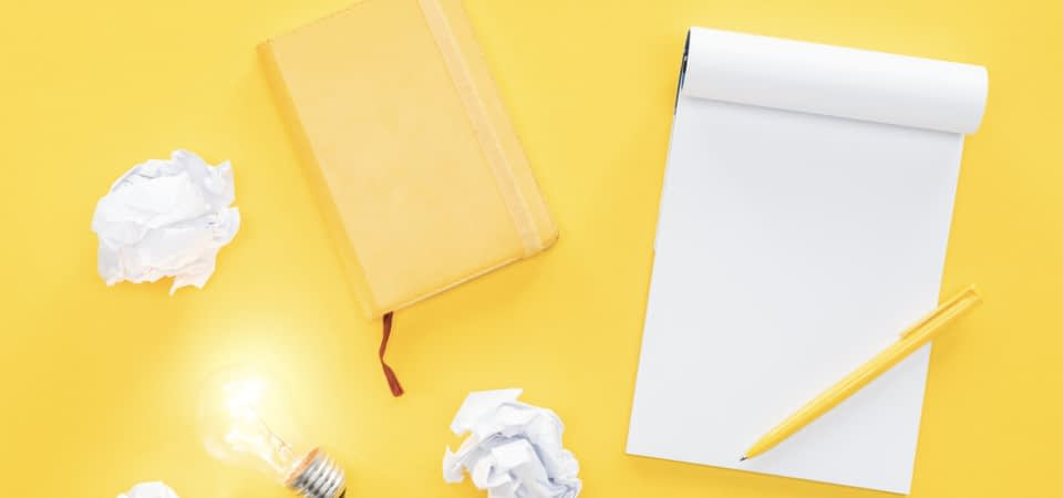 concept of writing ideas on yellow desk with yellow notebook, pad of paper, yellow pen, crumpled papers, and a lit up lightbulb