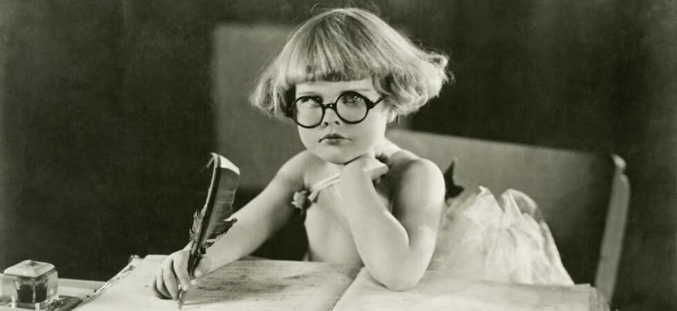 vintage photo of a young child holding a quill pen and frowning